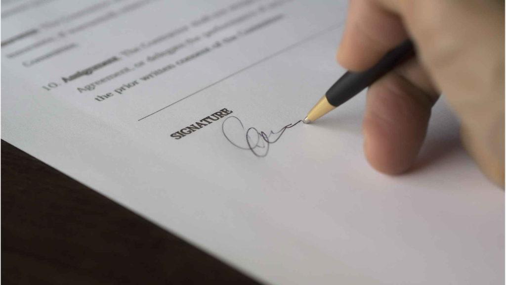 Человек подписывает ручкой документ.