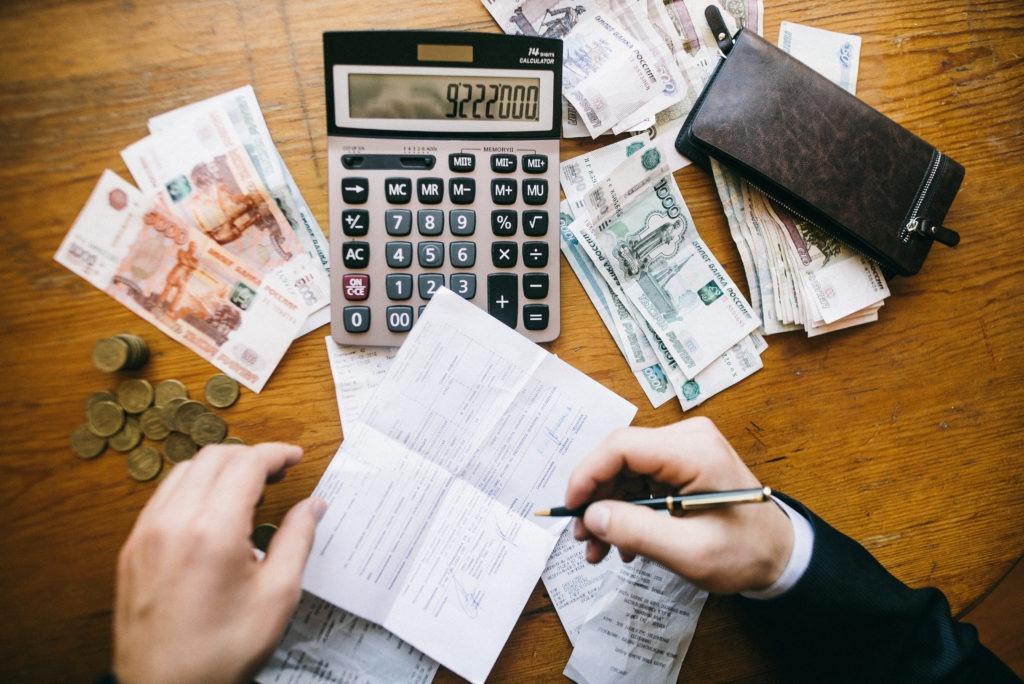 Человек считает с помощью калькулятора свои расходы и пишет их на листок