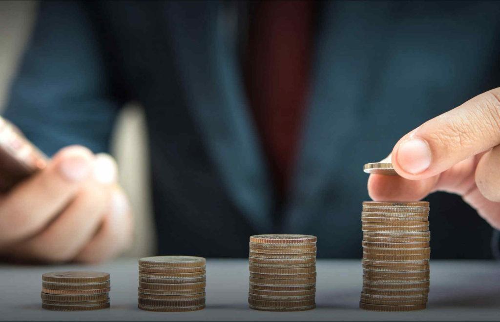 Человек складывает монеты в стопку на столе