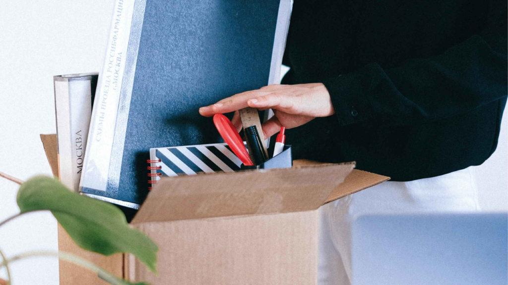 Человек собирает коробку с вещами с рабочего места