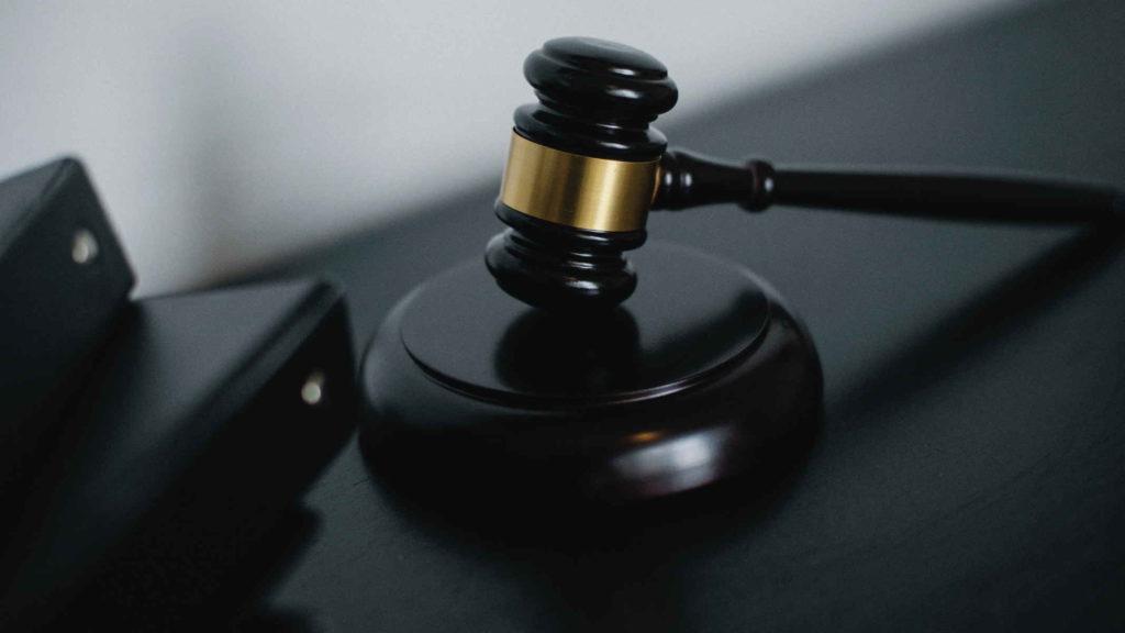 Черный судейский молоток на черном столе