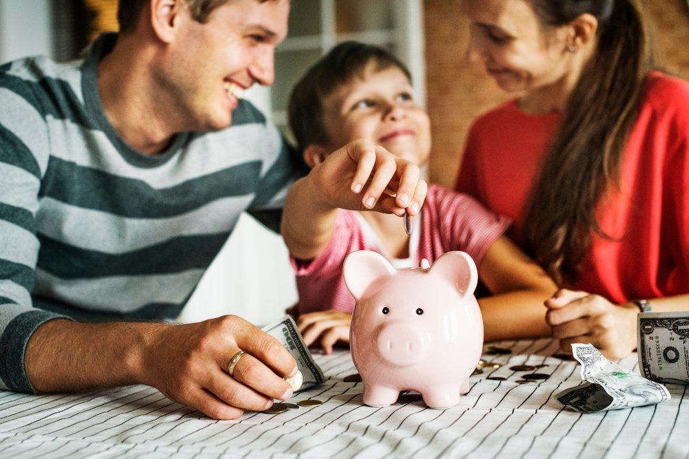 Члены семьи кладут деньги в копилку.