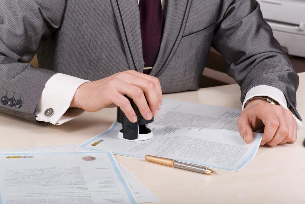 Мужчина в костюме ставит печать на документы.