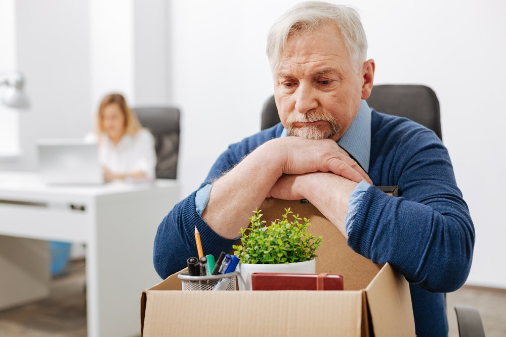 Грустный дедушка сидит над коробкой