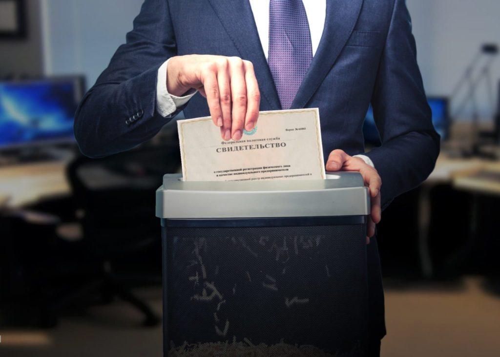 Мужчина бросает в шредер свидетельство о регистрации юридического лица.