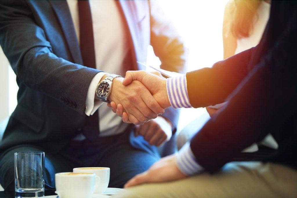 Мужчины в костюмах жмут друг другу руки