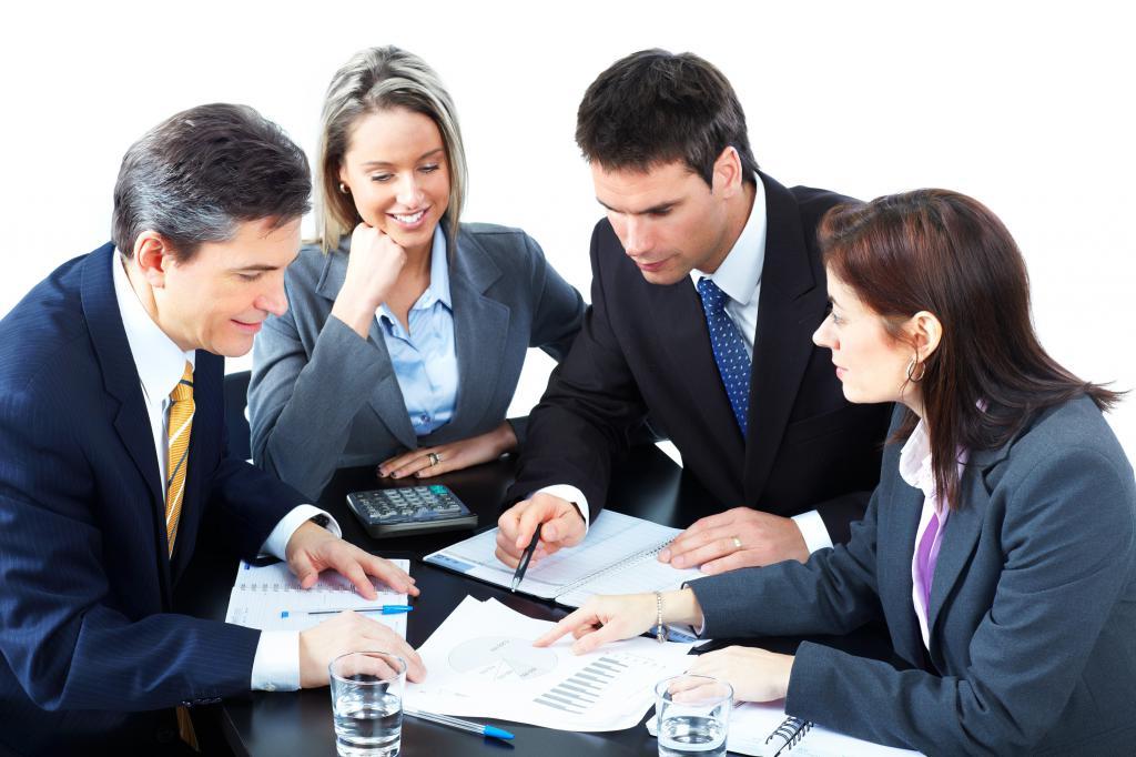 Офисные сотрудники сидят за столом и рассматривают графики