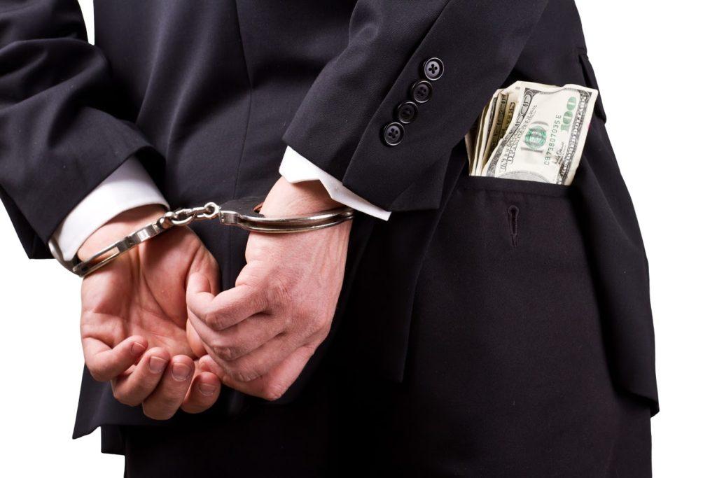 Мужчина в наручниках держит 100 долларов в кармане на белом фоне.