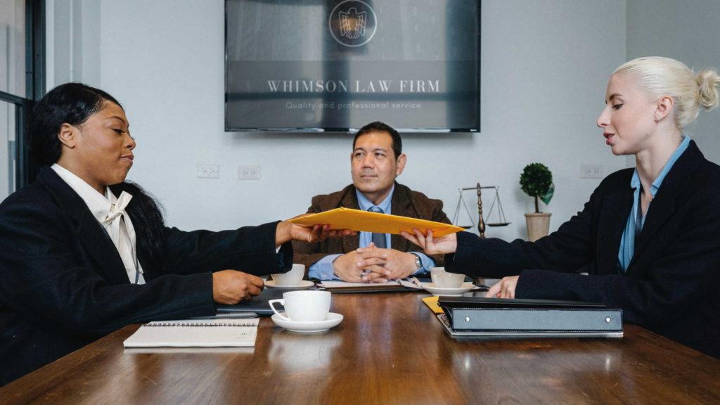 Работники сидят с начальником и обсуждают документы
