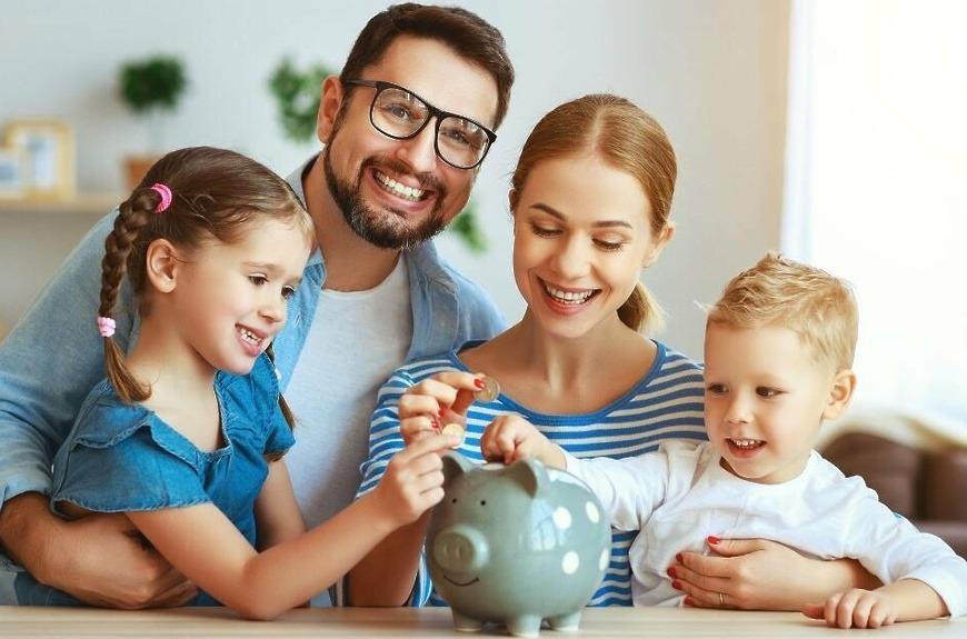 Семья улыбается и кладет деньги в копилку