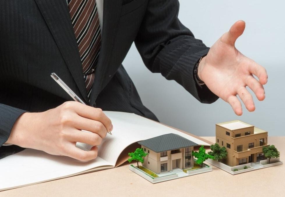 Мужчина подписывает документы на столе, на котором находятся домики.
