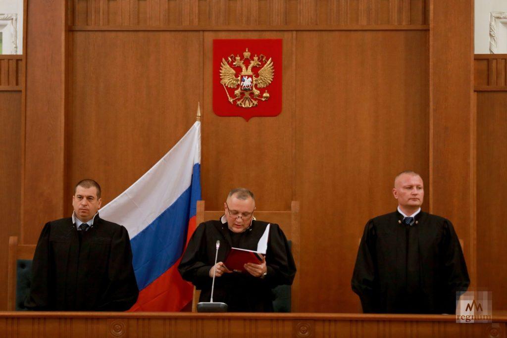 Трое судей в зале суда зачитывают судебное решение