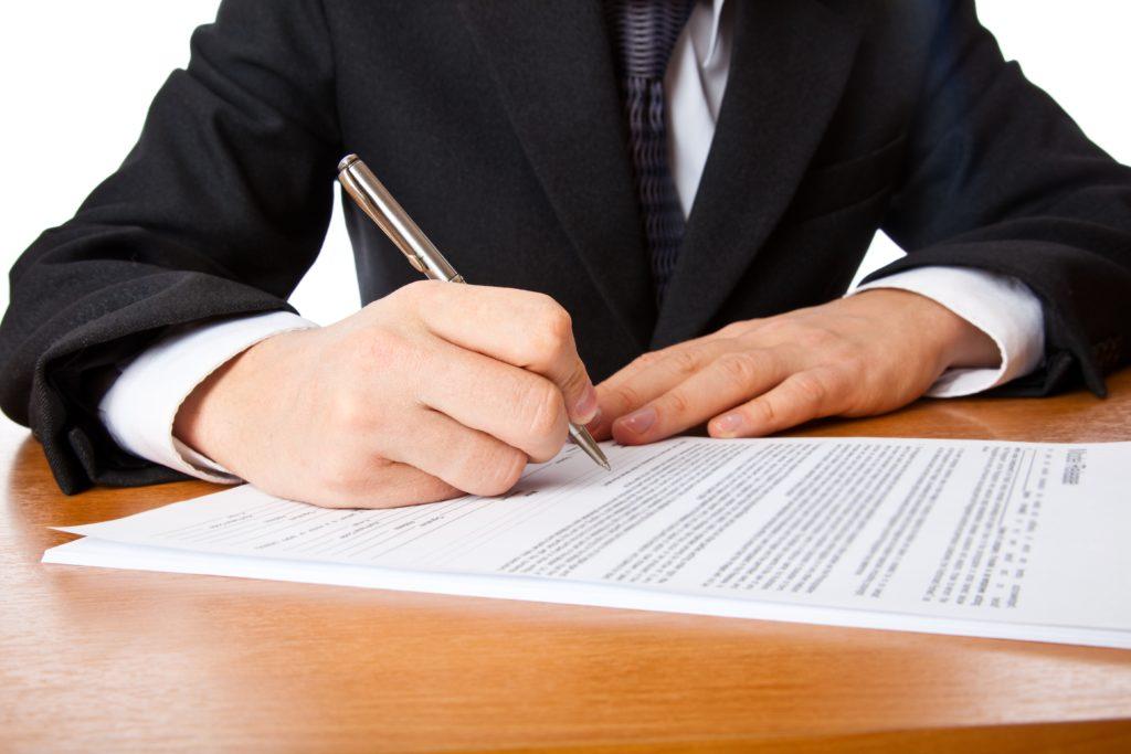 Мужчина в костюме подписывает документ.