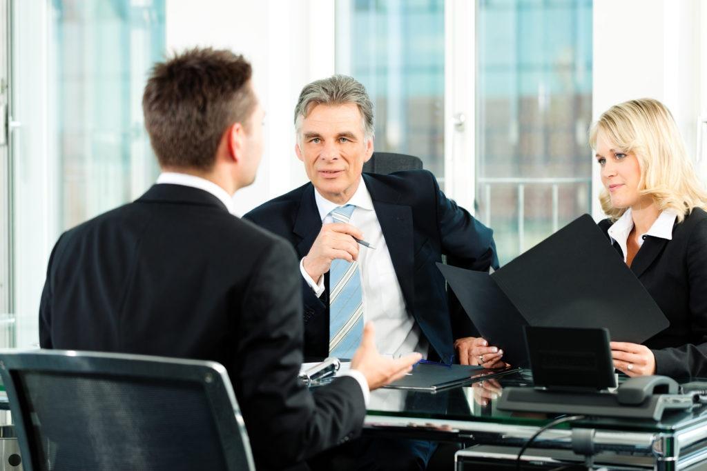 Люди в костюмах ведут переговоры в офисе.