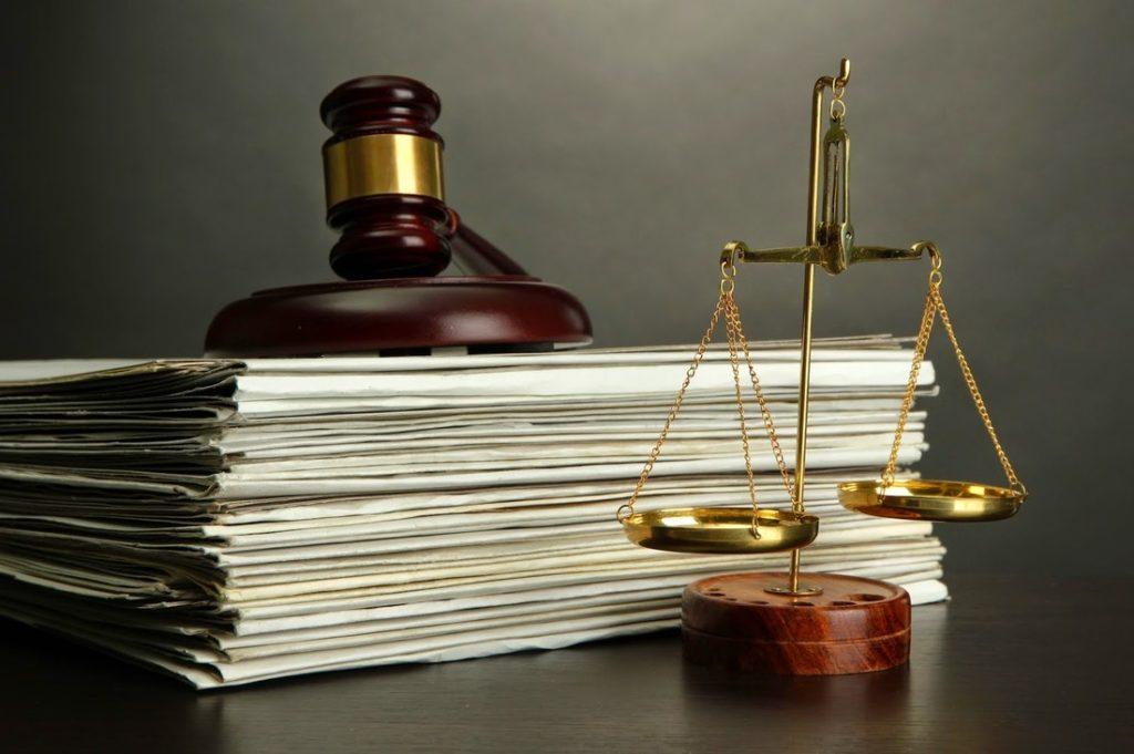 Весы фемиды и судейский молоток на столе