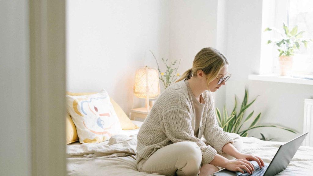 Девушка сидит на кровати и смотрит в компьютер