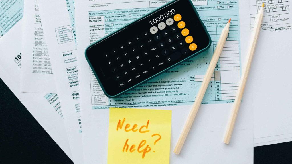 Калькулятор лежит на столе с расчетами