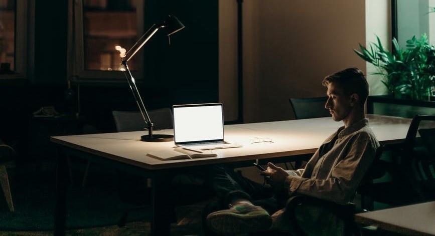 Человек сидит вечером в офисе