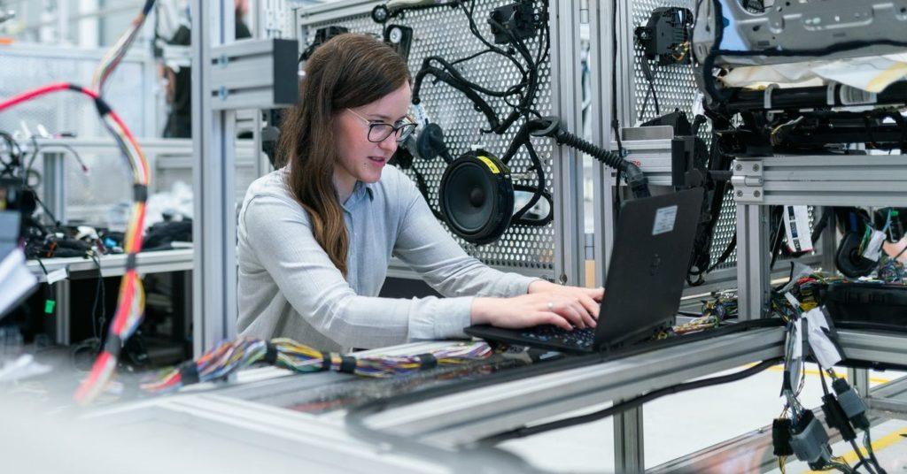 Девушка программирует на производстве