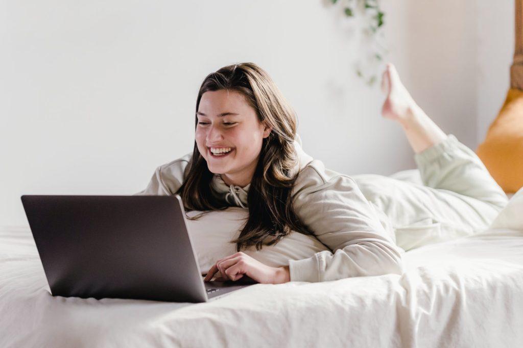 Девушка работает на кровати в ноутбуке