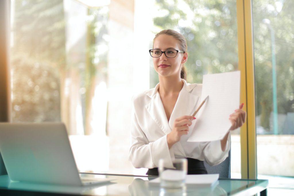 Девушка в кабинете показывает на договор