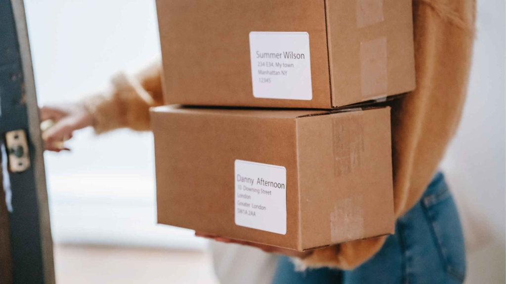Девушка заносит в квартиру посылки с почты
