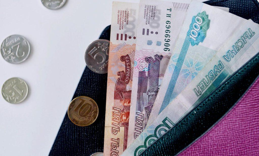 Купюры и монеты рублей лежат в кошельке