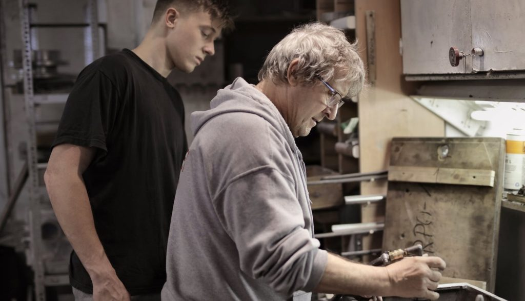 Мужчина обучает молодого парня работе на производстве