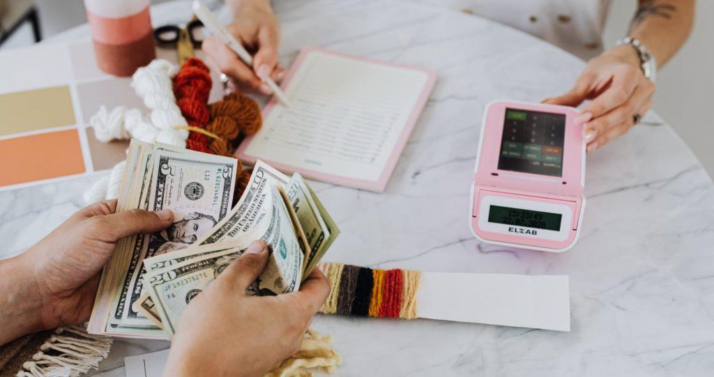 Один человек использует электронную кассу а другой считает деньги