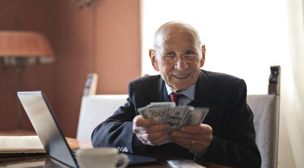 Пенсионер держит деньги в руках
