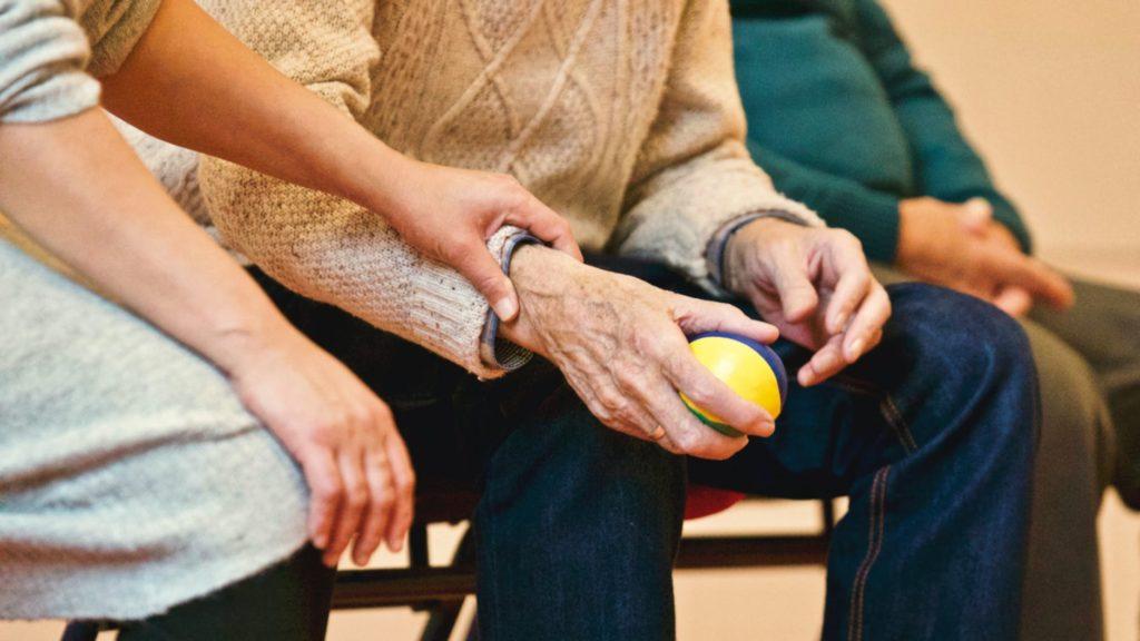 Пенсионер держит мячик в руках