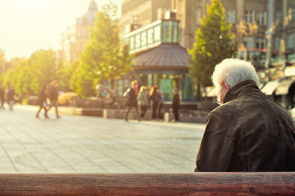 Пенсионер одиноко сидит на лавке