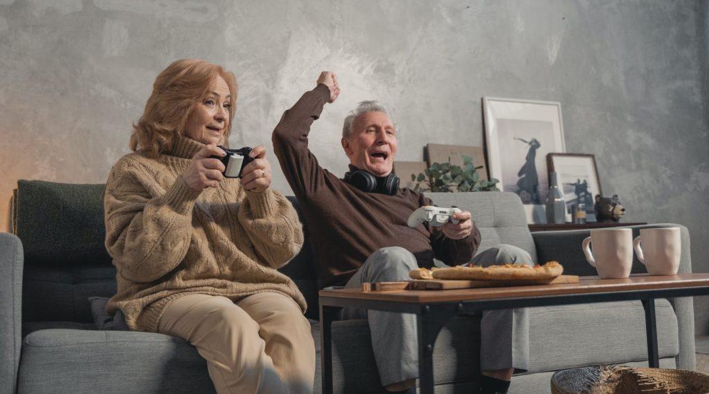 Пенсионеры играют в игровую приставку