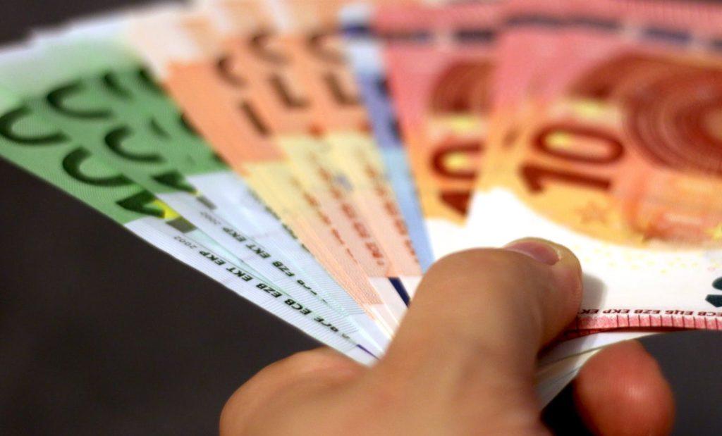 Рука передает деньги в пустоту