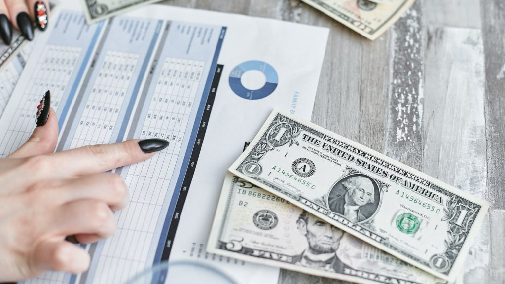 Рука показывает на график с акциями и деньги