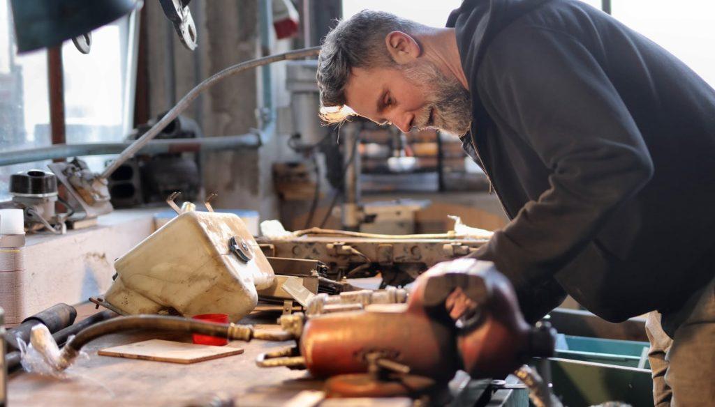 Седой мужчина работает на верстаке