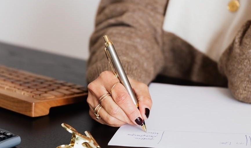 Женщина пишет заявление на столе от руки