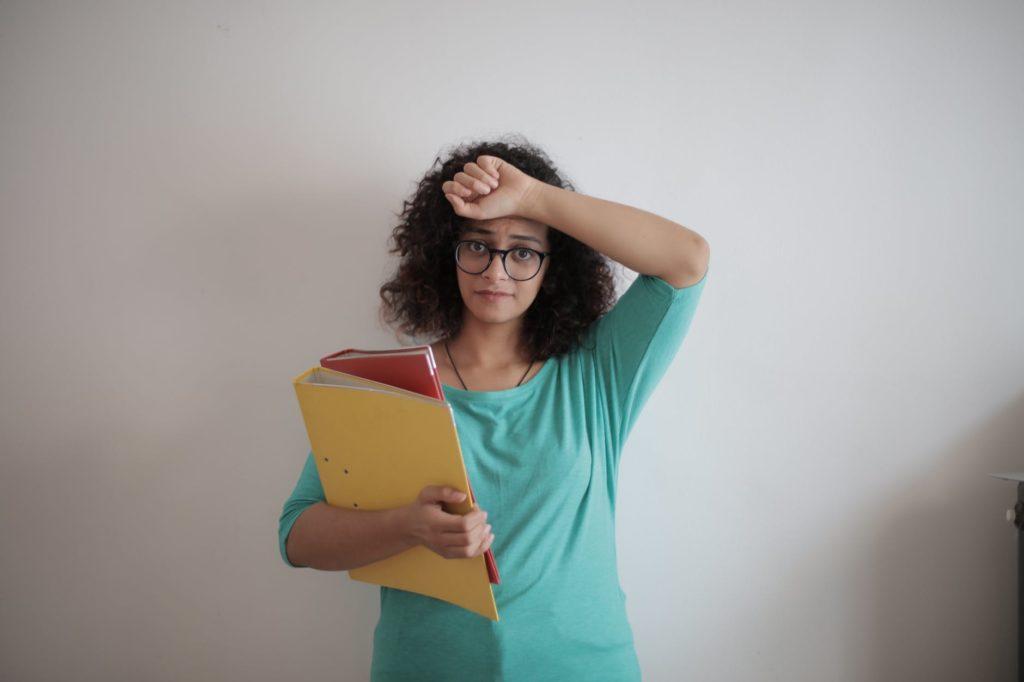 Женщина прикрывает лоб рукой и держит папки с документами