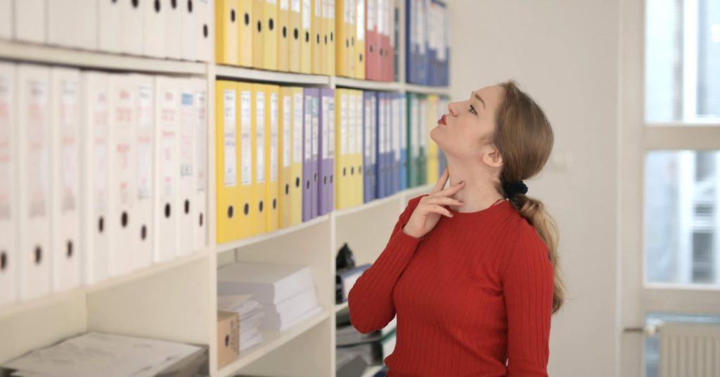 Женщина смотрит на папки с документами в бухгалтерии