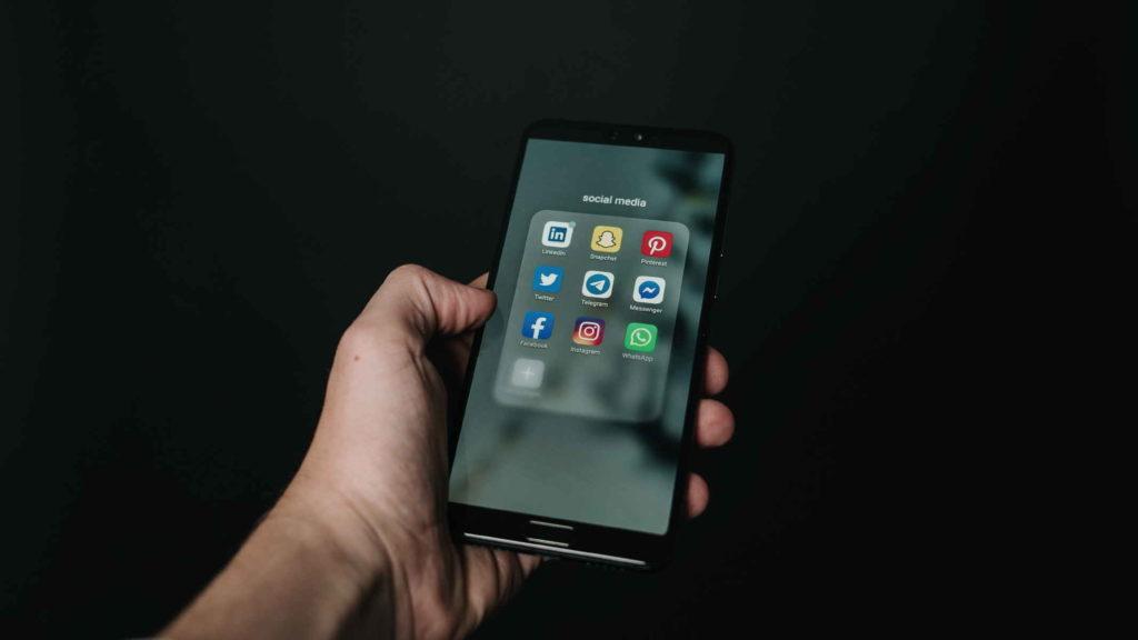 Человек держит в руке телефон с социальными сетями