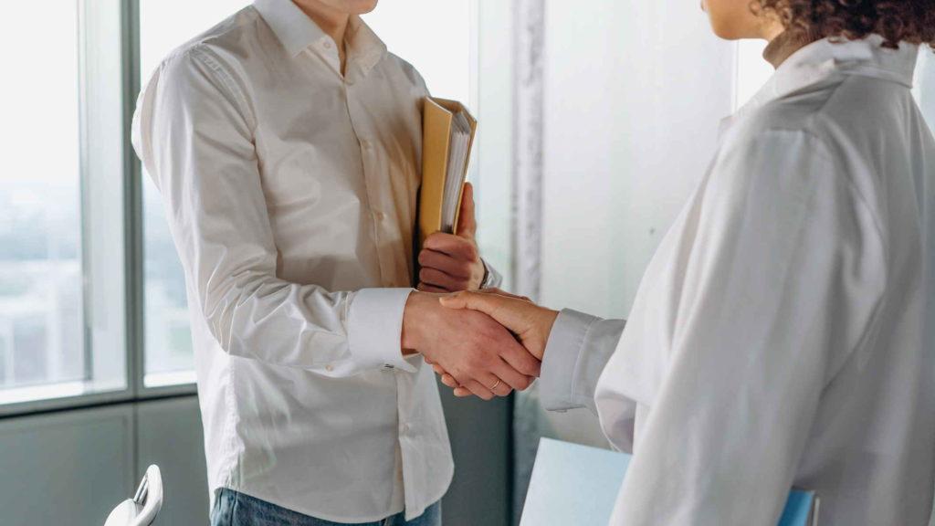 Мужчина жмет руку женщине врачу